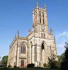 A large church seen from the northwest, showing a tower with clock faces over arches, an arched window, and crocketted pinnacles.