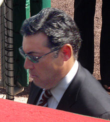 A dark-haired man wearing sunglasses, a dark jacket, and a red-and-white striped tie