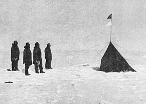 In an icebound landscape four figures stand, left, facing a small pointed tent from which two triangular flags are flying.
