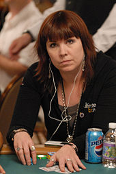 A woman with shoulder-length brown hair wearing a black jacket and jewelry, with white earphones hanging from her ears to the iPod that sits on the poker table in front of her. On the table are poker chips, cards, a soda can, and a small bottle of water.