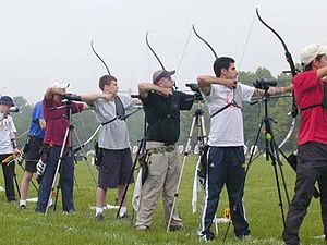 Recurve archers shooting in outdoor competition.