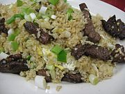 A plate of fried rice mixed with beef, scallions, and egg.