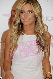 "A young female with long blonde hair wearing a white T-shirt with ""PROJECT PINK"" written on it smiles to the camera."