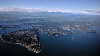 Bainbridge Island, Washington - Aerial view of Bainbridge Island from the southeast, showing the Bainbridge Island ferry from Seattle making the first of two turns to bring it into Eagle Harbor, with Blakely Harbor to its left
