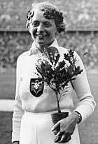 A black and white photograph of a female athlete in an all white outfit with the Nazi eagle and swastika in the middle of her chest. She holds a small plant and wears an laurel wreath on her head.