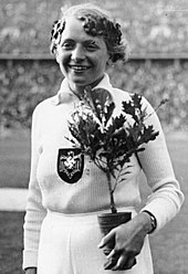 A black and white photograph of a female athlete in an all-white outfit with the Nazi eagle and swastika in the middle of her chest. She holds a small plant and wears an laurel wreath on her head.