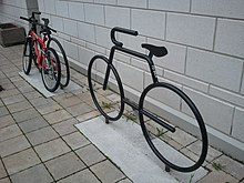 Two bicycle racks shaped like stylized bicycles, in metal with a gloss black finish, each set in a rectangle of concrete within a floor of small ceramic tiles, in front of a white-painted concrete block wall. The one in the background has a mountain bike chained to it.