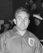 A black and white photograph of Billy Wright, wearing an England national team jersey.