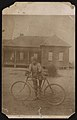 Boy standing next to a bicycle, house in the background LCCN2015652133.jpg