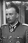 A black-and-white photograph of a man in semi profile wearing a military uniform and a neck order in shape of an Iron Cross.