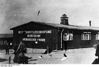 """Buchenwald Resistance - Buchenwald during liberation. The sign says, """"The German political prisoners welcome their American friends."""""""