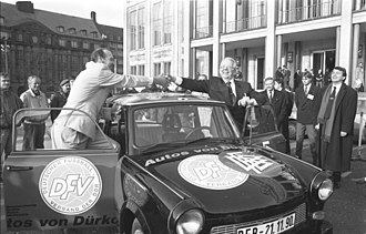 Deutscher Fußball-Verband der DDR - November 1990: Hans-Georg Moldenhauer, president of the NOFV, a subdivision of the DFV, receives a Trabant from DFB president Hermann Neuberger on the occasion of the DFV joining the DFB. The car is adorned with both logos.