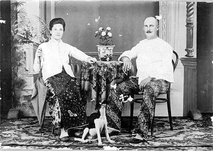 COLLECTIE TROPENMUSEUM Studioportret van een Europees echtpaar gekleed in saroeng kabaja en ochtendbroek TMnr 60048827
