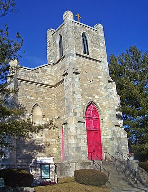 "A narrow light brown stone building with a red door in a pointed arch. Above it is a square tower with a cross on top. A small sign in front says ""Calvary Baptist Church""."