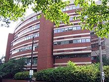 Un edificio de seis pisos de ladrillo circular con rayas decorativas de hormigón blanco encima y por debajo de las líneas de ventanas cuadradas adyacentes que rodean la mayor parte de cada nivel
