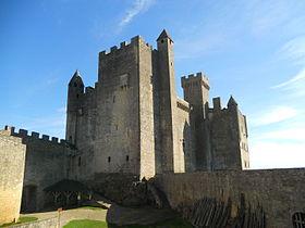 Photographie en contre-plongée de la partie principale d'un château-fort aux pierres de couleur grise.