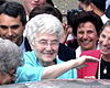 Chiara Lubich, smiling, surrounded by other smiling people.