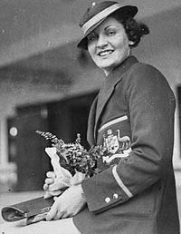 Young woman with short wavy hair, in a straw circular hat with ribbon, wearing a ceremonial blazer with the Australian coat of arms, and holding a bouquet of flowers and paper documents.