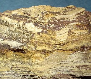 Corderoite - Dark red bands of cinnabar alternate with layers of tan limonite. The corderoite are the yellow-tan microcrystals.