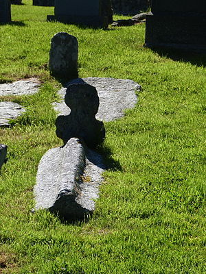 Unst - Small cross-shaped marker with a grave stone shaped like the keel of an inverted ship at the late-Norse Christian Chapel at Framgord, Sandwick