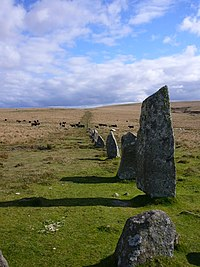 Line of upright, angular stones receding into rolling, grassy terrain