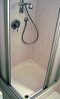 Shower place in which a person bathes under a spray of water