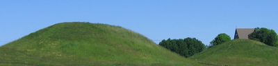 Eadgils was buried at Uppsala, according to Snorri Sturluson. When Eadgils' mound (to the left) was excavated, in 1874, the finds supported Beowulf and the sagas. They showed that a powerful man was buried in this large barrow, c 575, on a bear skin with two dogs and rich grave offerings. These remains include a Frankish sword adorned with gold and garnets and a tafl game with Roman pawns of ivory. He was dressed in a costly suit made of Frankish cloth with golden threads, and he wore a belt with a costly buckle. There were four cameos from the Middle East which were probably part of a casket. A burial fitting a king who was famous for his wealth in Old Norse sources. Ongen�eow's barrow to the right has not been excavated.