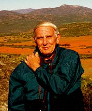 Edward M. Burgess pictured in Namaqualand, South Africa.  Burgess is wearing a dark blue-green jacket and is carrying a camera strapped around his neck (tourist style).  His left arm is positioned across his chest with his left hand on his right shoulder. Burgess is looking directly into the (active) camera with a slight smile.  In the background are numerous mountainous peaks breaking to a pale blue sky at the top of the photo.  At approximately shoulder height the green vegetation in the foot hills gives way to an expanse of orange-red flowers.