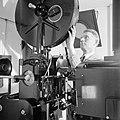 Een personeelslid plaats een film in de projector, Bestanddeelnr 255-7792.jpg