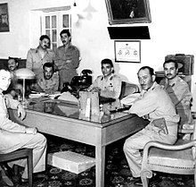Eight men in dressed in military uniform, posing in a room around a rectangular table. All the men, except for third and fifth persons from the left are seated, the third and fifth person from the left are standing.