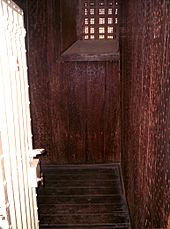 Cell with walls and floor covered in Jarrah, held with an abundance of nails
