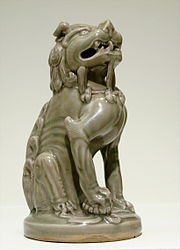 A small, green-grey statuette of a lion, sitting down and looking upwards. The lion's limbs are thin and angular.
