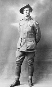 A full body portrait of a standing man. He is wearing a military uniform, a slouch hat and has a medal pinned to his left breast. His arms are behind his back and his right leg is forward. Three stripes can be seen on his right sleeve, denoting his rank as sergeant.