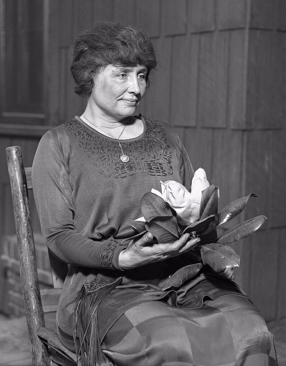 Helen Keller holding a magnolia, ca. 1920