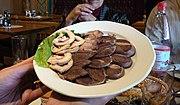 Assiette contenant des rondelles de saucisses de viande et de graisse