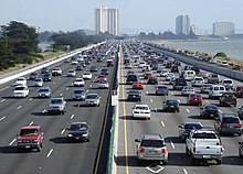 Looking down a straight busy ten-lane highway running along a coastline. In the background are a few multi-story buildings.