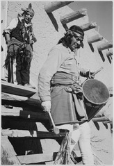 "Indian descending wooden stairs with drum, another in background looking on, ""Dance, San Ildefonso Pueblo, New Mexico, 1 - NARA - 519977.tif"