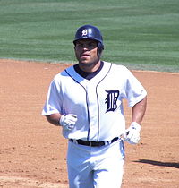 A baseball player in uniform runs across the infield.