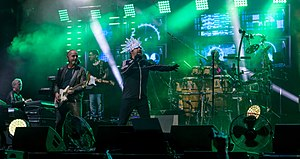 A band all dressed in dark clothing performing on stage; a singer with a white LED head-dress, two guitarists, a keyboardist, and a bongo player are seen behind fog coloured green from the stage lighting.