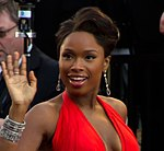 Headshot of an African-American female in her late twenties wearing a red dress. She is waving her right hand.