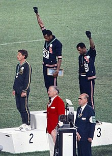 8606b50dd52f PUMA sponsored Gold medalist Tommie Smith (center) and bronze medalist John  Carlos (right) showing the raised fist on the podium after the 200 m race  at the ...