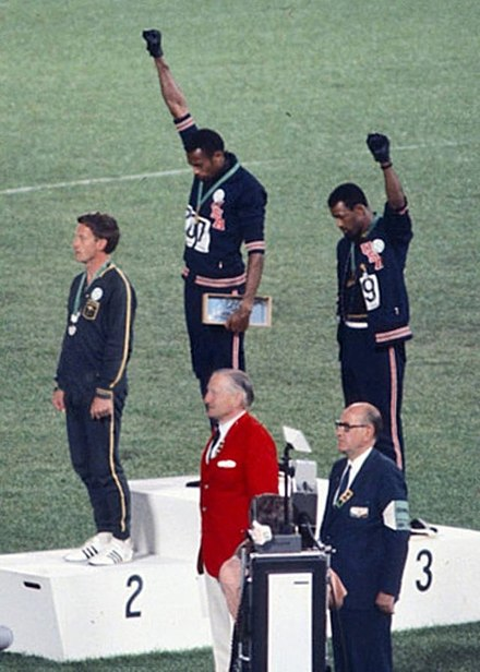 Gold medalist Tommie Smith (center) and bronze medalist John Carlos (right) showing the raised fist on the podium after the 200 m race at the 1968 Summer Olympics; both wear Olympic Project for Human Rights badges. Peter Norman (silver medalist, left) from Australia also wears an OPHR badge in solidarity with Smith and Carlos. John Carlos, Tommie Smith, Peter Norman 1968cr.jpg