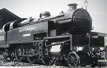 Side-and-front view of the 3-cylinder version of the locomotive. The distinguishing feature is a full-width flat panel rising vertically above the front buffer beam to the level of the bottom of the smokebox door. The water tanks are a different shape from the K Class, as they include a rectangular access hole in the side, bottom-front, for maintaining the valve gear, which is also different from the K class.