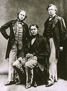 Three middle-aged men, with the one in the middle sitting down. All wear long jackets, and the shorter man on the left has a beard.