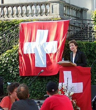 Flag of Switzerland - Former Federal Councillor Elisabeth Kopp speaking on 1 August 2007. The federal flag displayed here has a narrower margin than recommended in the flag regulation, with a ratio of cross to flag width of about 5:7 instead of the recommended 5:8.