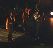 Three women sing on stage. They wear similar outfit (a dark blouse and trousers).