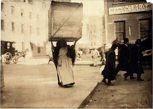 Lewis Hine, Italian woman carrying enormous dry-goods box, New York, 1912
