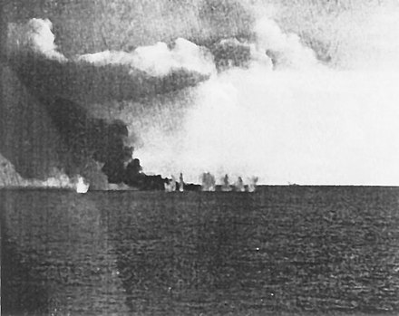 USS Gambier Bay, burning from earlier gunfire damage, is bracketed by a salvo from a Japanese heavy cruiser (faintly visible in the background, center-right) shortly before sinking during the Battle off Samar. LeyteGambierBayStraddle.jpg