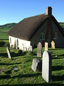 A large thatched building surrounded by gravestones, set into a hillside which slopes down towards green fields