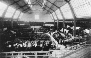Darkened interior of a large hall with two rows of high windows along each side. It is possible to discern a seated orchestra in the foreground, with mass choirs in the background.